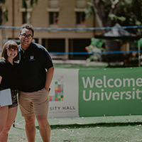 Two students standing with welcome to unihall sign