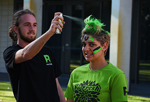 UniHaller getting her hair sprayed in the green college colour