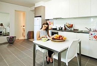 Female resident sitting at table in one bedroom apartment kitchen