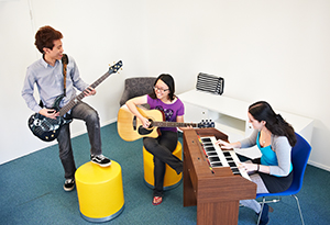 Residents jamming out in the music room on guitar and piano