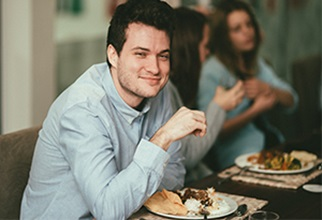 Male resident enjoys meal with peers and faculty at Academic Dinner
