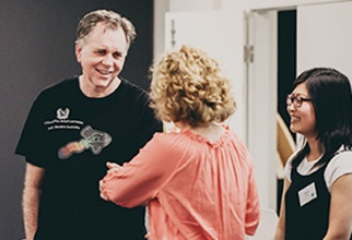 Professor Barry Marshall shaking hands with female resident at leadership event