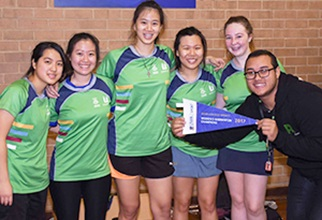 The winning female badminton team proudly holding their flag