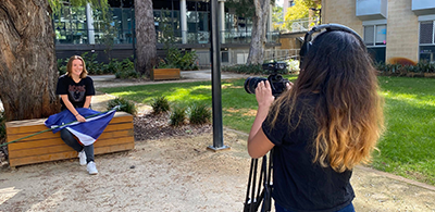 Image of student holding their national flag being filmed for the Language Videos